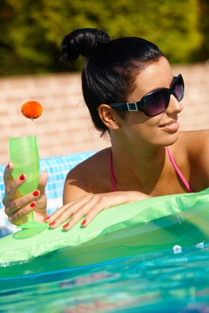 Attractive young woman in pool at summertime, drinking cocktail, looking away. photo