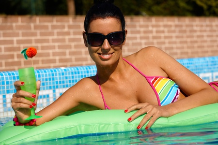 Sexy woman laying on airbed in swimming pool, smiling, sunbathing. photo