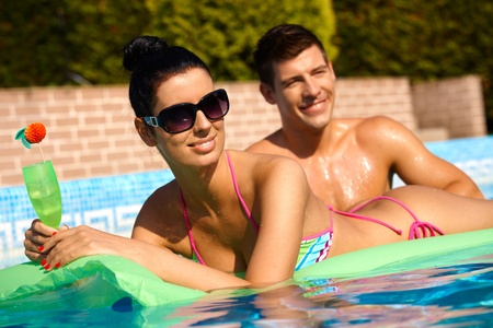 Young people in swimming pool at summertime, smiling. photo