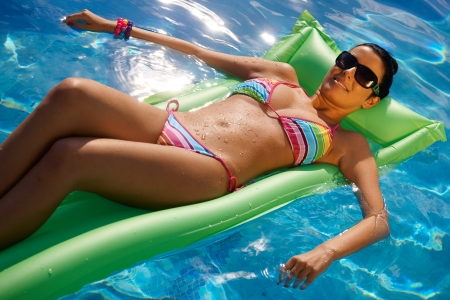 lying on back: Sexy young woman laying on airbed in bikini in middle of pool.