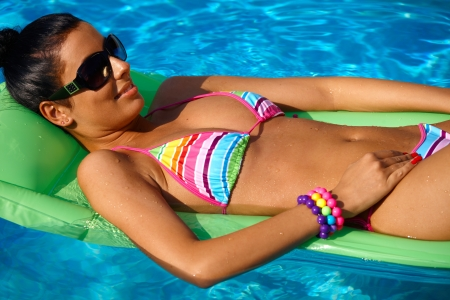 summer vacation bikini: Pretty young woman sunbathing in swimming pool, laying on airbed.