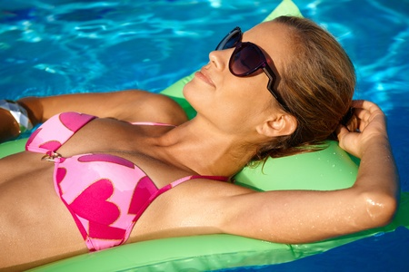 Young woman sunbathing in swimming pool at summertime, laying on airbed. photo
