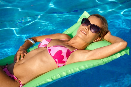 lay down: Pretty young girl laying on airbed in swimming pool, relaxing, sunbathing.