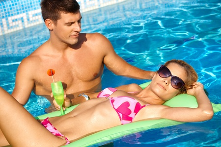 Romantic couple in outdoor pool at summertime. Stock Photo - 12918682