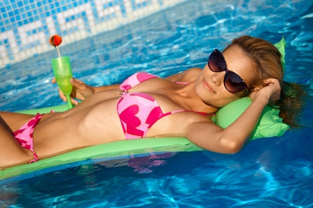 lay down: Sexy girl in bikini relaxing on water at summertime, laying on airbed in pool.