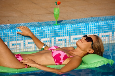 Young woman laying on airbed in swimming pool, enjoying summer holiday. photo