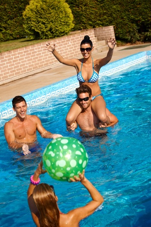 pool ball: Happy young people playing in swimming pool, having fun. Stock Photo