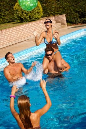 vibrant colors fun: Giovani amici che giocano a pallone in acqua, ridere, divertirsi in estate.