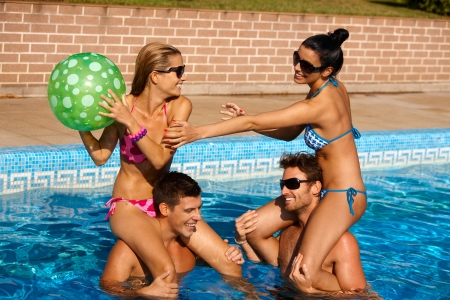 Young couples having fun on summer holiday in swimming pool, laughing. photo