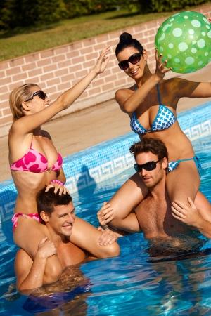 compa�erismo: Compa��a joven feliz divirti�ndose en la piscina al aire libre en verano.