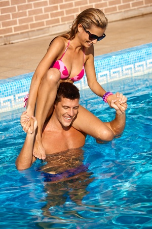 Happy young couple having summer fun in outdoor swimming pool. photo