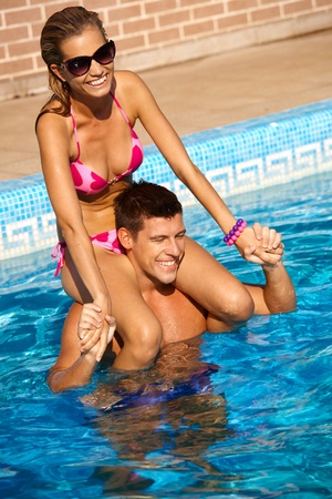 have on: Attractive young couple enjoying summer holiday in swimming pool, smiling, having fun.