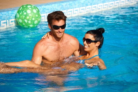 Romantic young couple having fun in swimming pool, enjoying holiday, smiling. photo