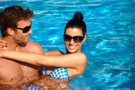 Attractive young couple refreshing in outdoor pool at summertime, smiling. photo