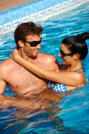 Loving couple enjoying summer holiday in swimming pool, smiling. photo