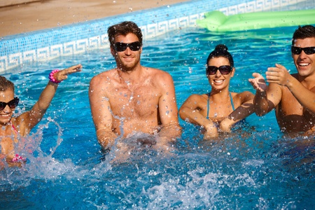 outdoor photo: Young companionship splashing in outdoor swimming pool, having fun.