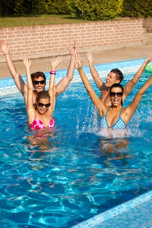companionship: Happy young companionship having summer fun in outdoor swimming pool. Stock Photo