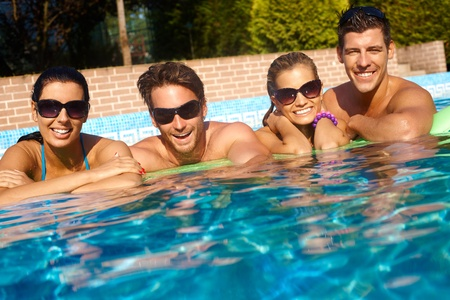 sunlit: Happy young couples smiling in outdoor swimming pool at summertime.