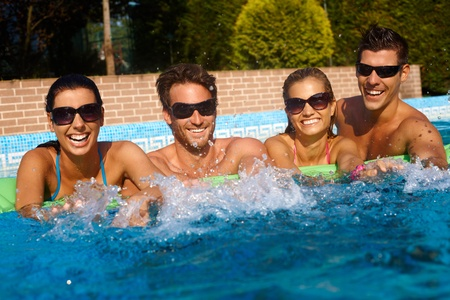 Happy friends having fun in outdoor swimming pool at summertime, laughing. photo