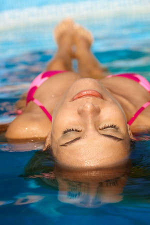 Pretty woman sunbathing in water eyes closed. photo