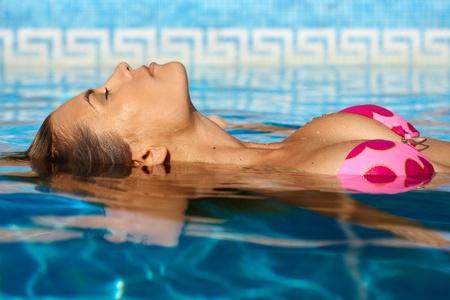 屋外スイミング プールで夏の太陽を楽しんでセクシーな女性。