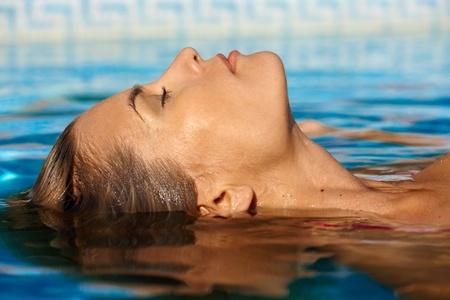 Mujer joven que disfruta del agua y el sol en la piscina exterior. Foto de archivo
