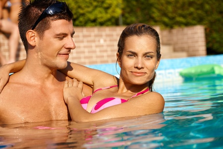 Attractive young couple smiling in swimming pool at summertime. Stock Photo - 12918703