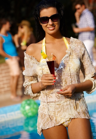 Beautiful woman on summer holiday with cocktail in hand, smiling. photo