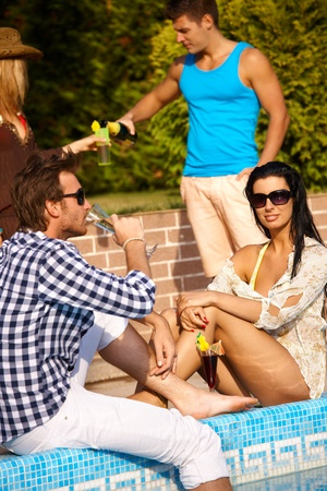 Young people on summer holiday by swimming pool, drinking having fun. photo
