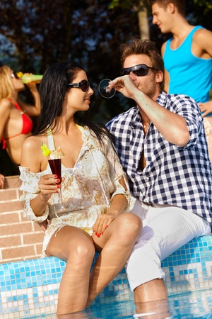 Romantic young couple by swimming pool having drinks, smiling. photo
