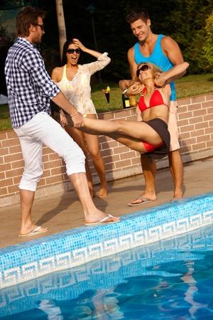 compa�erismo: El compa�erismo feliz que se divierte en el verano por la piscina. Foto de archivo