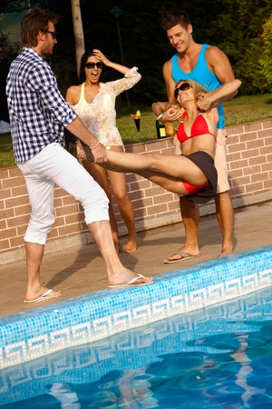 vibrant colors fun: Happy companionship having fun at summertime by swimming pool.