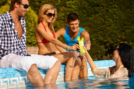 pool party: Happy young friends having drinks at swimming pool, smiling, enjoying holiday.