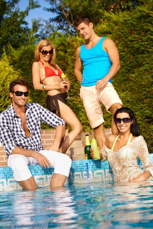 pool party: Attractive young people enjoying summer holiday by outdoor swimming pool, smiling.