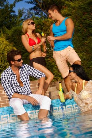 fiesta amigos: Feliz pareja de j�venes se divierten en la piscina.