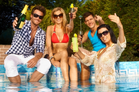 friends party: Cheerful young people sitting by swimming pool, drinking, having fun, enjoying holiday.