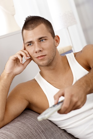 Sporty guy relaxing at home in singlet with remote control handheld, watching tv, small smile. photo