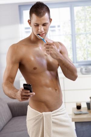 seminude: Sexy muscolare semi-nude giovane in piedi in un asciugamano in salotto, lavaggio denti e usando il telefono cellulare, sorridendo.