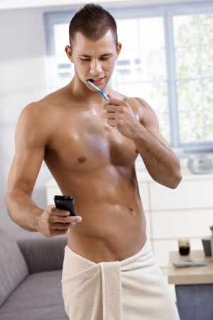 Sexy muscular semi-nude young man standing in towel in living room, washing teeth and using mobile phone, smiling. photo