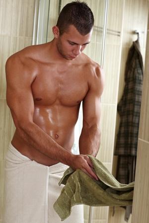 seminude: Muscolare semi-nude giovane asciugatura delle mani con un asciugamano, il giovane corpo sportivo sexy.