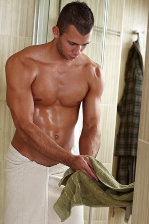 wet men: Muscular semi-nude young man drying hand with towel, young sporty sexy body.