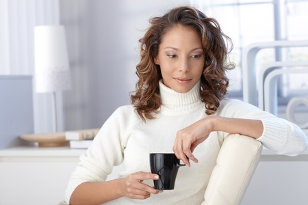 Young ethnic woman drinking coffee at home, looking down. photo