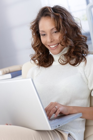 woman sweater: Happy woman using laptop computer, working, browsing internet.