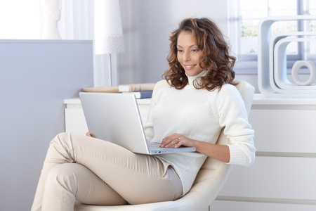 woman sitting with laptop: Pretty young woman using laptop computer at home, sitting in modern chair, smiling. Stock Photo