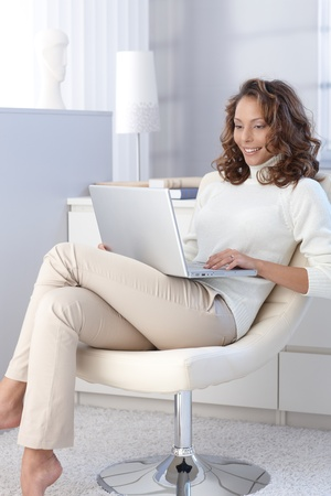 Attractive female working on laptop computer at home. Stock Photo - 13061167