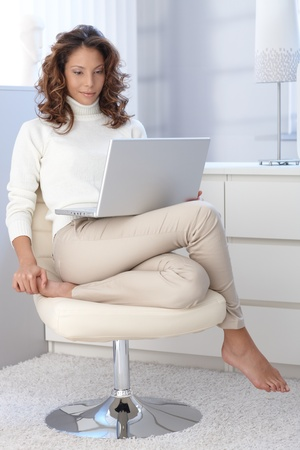 Pretty woman using laptop computer, sitting in modern chair at home. Stock Photo - 13061166