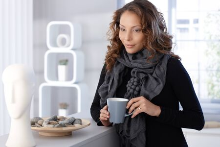 Pretty woman drinking coffee at home, thinking. Stock Photo - 13061219