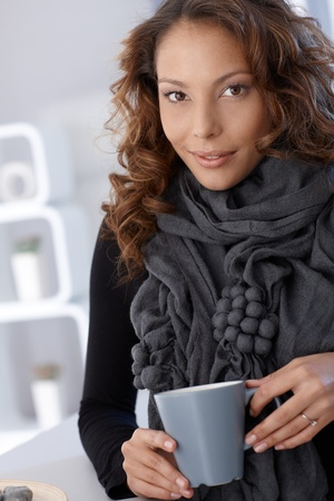 Portrait of young attractive female drinking tea, looking at camera. photo