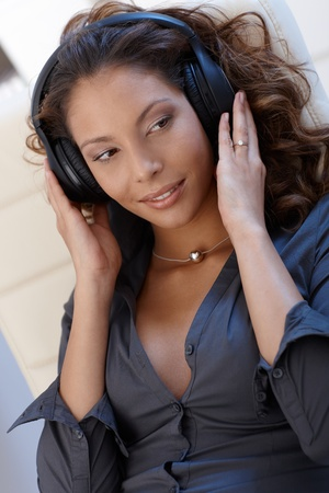 Sexy ethnic woman listening to music through headphones. photo