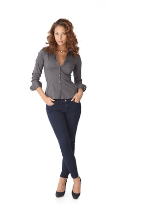 standing alone: Pretty girl standing legs crossed over white background. Full length.
